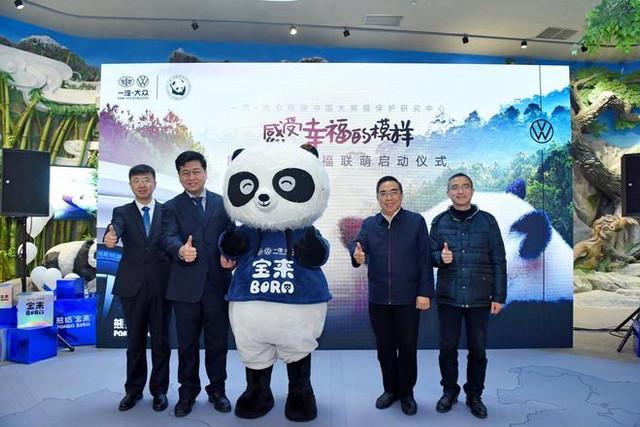 """一汽-大众销售有限责任公司副总经理 马振山从中国大熊猫掩护研究中间常务副主任  张和民手中接过印有""""熊猫宝来""""掌印的合作授权牌"""