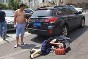 女子就要被车碾 路人徒手推车
