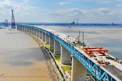 Workers pave asphalt on surface of Shanghai-Nantong Railway Bridge in China's Jiangsu