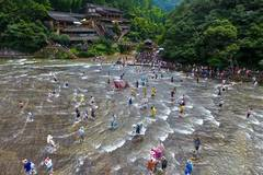 People cooling themselves in shallow water at scenic spot in China's Fujian