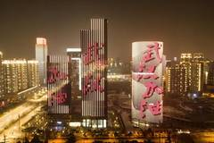 Builldings illuminated with slogans to cheer up Wuhan