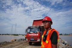 Staff members work at construction site of breached dyke in Poyang Town