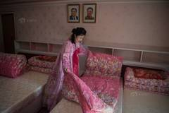 North Korean female workers display new dormitory in traditional costume