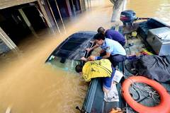 Policemen transfer people trapped by flood in S China's city