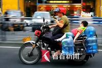 父亲边玩手机边骑摩托 后座小孩躺着睡觉