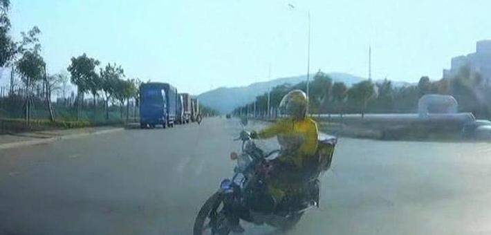 外卖员技能高超边开摩托车边看手机