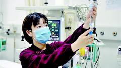 女护士跪在移动抢救车上为猝死患者不停做心肺复苏