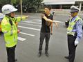 交警向回到现场的司机了解情况。