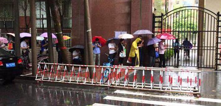 郑州小学报名首日 家长雨中排队