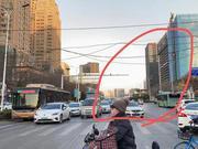 赞!郑州闹市街口电缆垂落 交警徒手托举保通