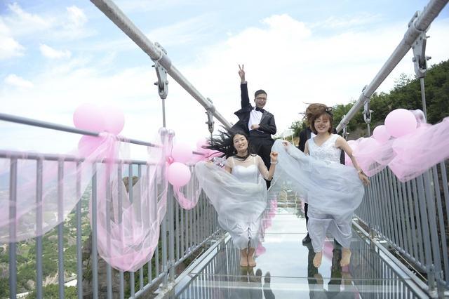 身着学士服在湖南平江石牛寨透明玻璃桥上拍起了高空创意毕业照,以此