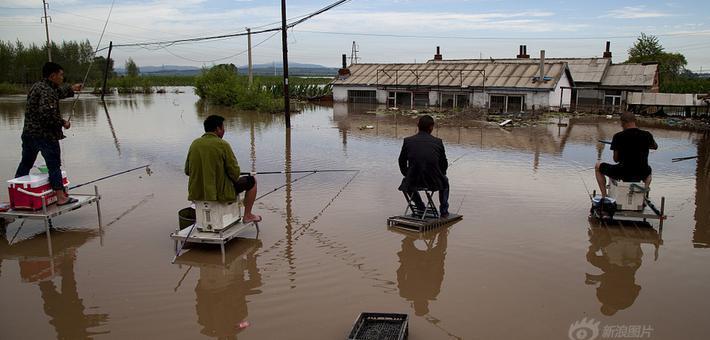 吉林洪涝现场 居民坐在院子中钓鱼