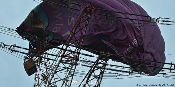 德国热气球挂高压线塔上 6人被困70米高空(图)