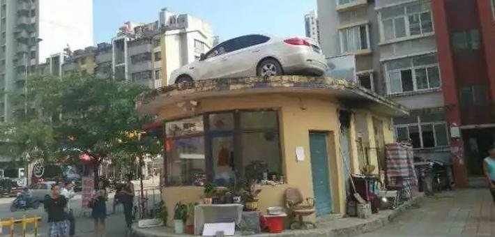 女子用轿车堵小区门 车被吊上房顶