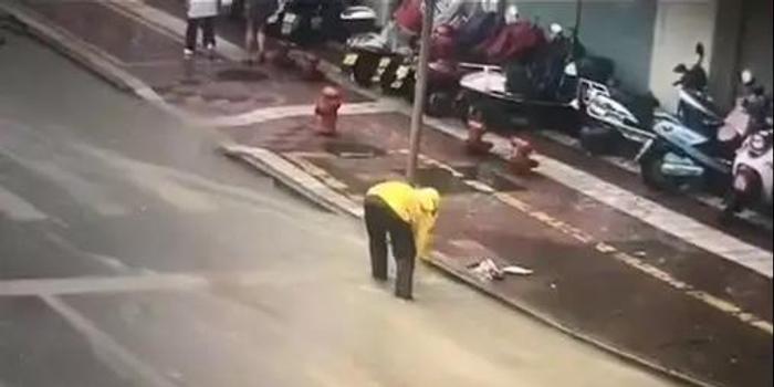 台风天送单 外卖小哥途中清理下水口排路面积水
