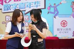 People experience digital RMB at Happy Valley Beijing theme park