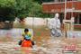 洪水围困乡村小学 学童骑在救援人员肩上撤离