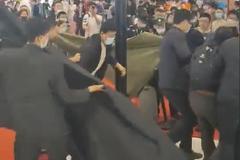 上海車展特斯拉展臺再現維權:黑布、黑傘齊上陣 維權者被大漢秒制服