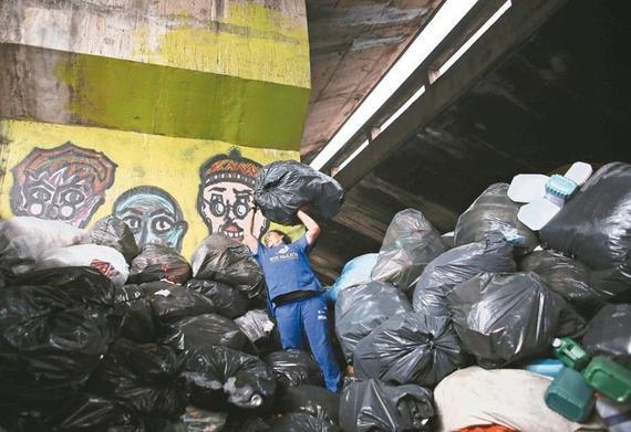 图为巴西圣保罗市一位渣滓搜集员高举大袋废物堆积。 路透