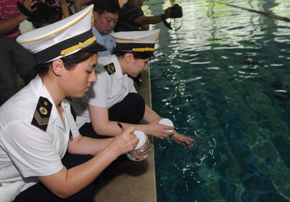 北京市卫生监督所的工作人员在某游泳馆取样(资料图)