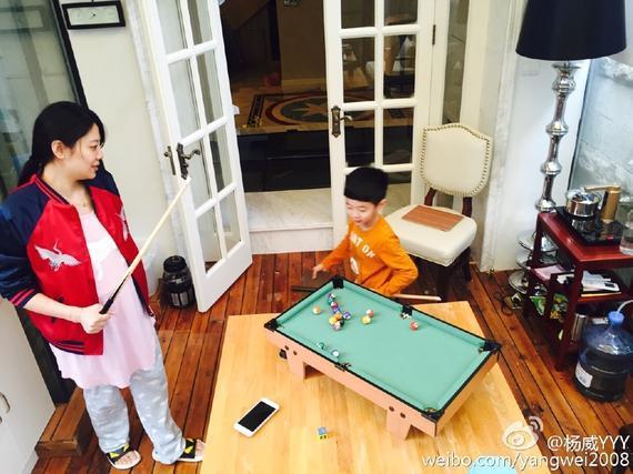 妈妈杨云挺着大肚子耐心地指导杨阳洋打桌球。
