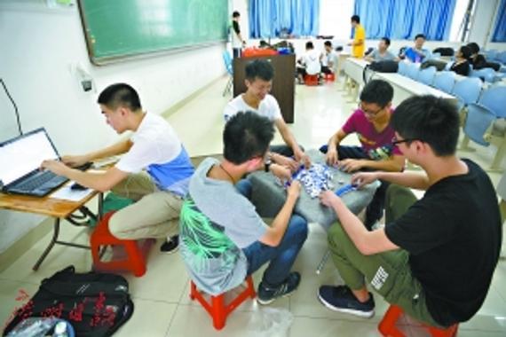 教室里正在举行竞技麻将比赛;一局结束,裁判就用电脑记录下成绩。