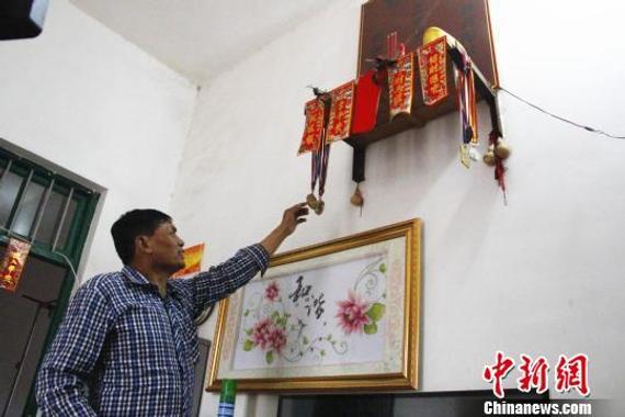 莫有雪的父亲莫土正介绍挂在家中的奖牌。