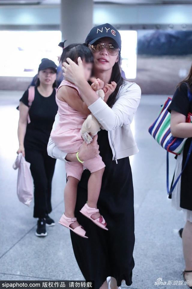 6月8日,姚晨一家人四口现身北京机场。姚晨帽子墨镜遮面,宽松的黑色连衣裙外搭小开衫非常休闲。女儿小茉莉穿粉红色的连衣裙,梳两个小辫子软萌可爱。姚晨非常熟练地抱着小茉莉,为小茉莉护头妈妈力满分。