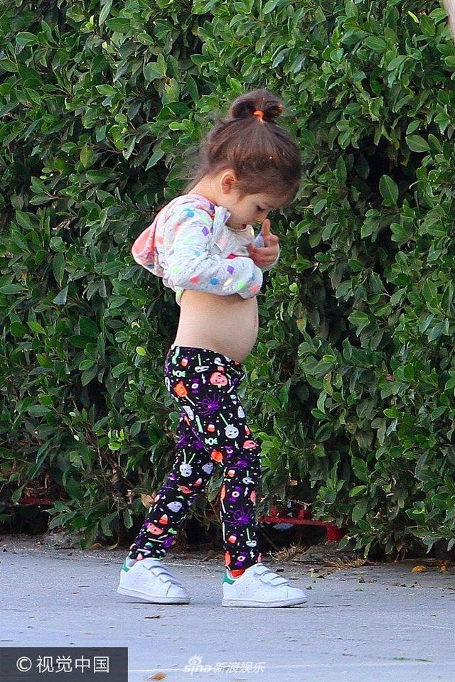 """美国洛杉矶,米拉·库尼斯(Mila Kunis)和孩子现身街头。米拉·库尼斯一身干练的黑白配出街,气场全开,甜美可爱的女儿边走边撩衣服""""观察""""肚肚,好奇心十足。"""