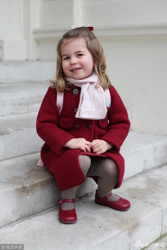 """1月8日,英国伦敦,英国夏洛特小公主迎来幼儿园第一天,出门前在肯辛顿宫拍照,背上小书包一脸乖巧。夏洛特小公主入读""""威尔科克斯幼儿园""""。"""