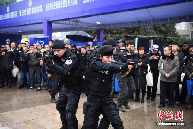 """1月10日,重庆特警持枪进行战术表演气场十足。当日,重庆市公安局在观音桥步行街开展了""""110宣传日""""主题活动。活动现场分为110在您身边、平安建设、民生警务、警通联动四个专区板块。来自治安、交巡警、刑侦、经侦、出入境等16个直属单位的民警在此搭设展台,为市民提供各种现场体验项目。陈超 摄"""