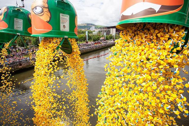 """6月18日,西班牙北部的毕尔巴鄂市的河道上举行了""""第五届小黄鸭游泳比赛"""",共有三万只橡皮小黄鸭参赛。当天下午1点半,三万只参赛橡皮小黄鸭被从桥上投入河渠内。"""