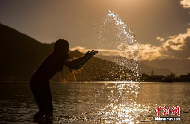 """9月12日晚,藏族民众在拉萨河边戏水。9月9日至15日,西藏民众迎来一年一度的""""沐浴节"""",藏语称""""嘎玛日吉"""",意为洗澡。民间相传,""""沐浴节""""洗浴的最佳时间是在夜幕降临之后,在星空下洗浴效果最好,可以洗去疾病,也能带来吉祥和好运。""""沐浴节""""是一个在拉萨、日喀则、山南等地藏民族中具有八百多年悠久历史的节日。一般在藏历七月六日至十二日举行,历时7天。中新社记者 何蓬磊 摄"""