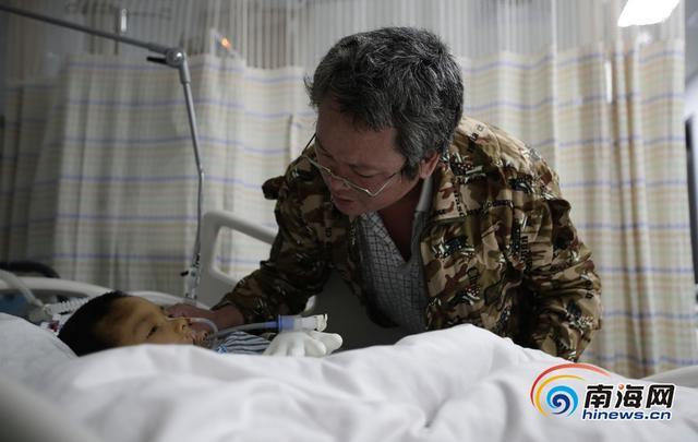 """11月12日上午11点44分,海口6岁""""懂事娃""""房小龙第三次躺在了海南省医学院第二附属医院的手术台上,但这次,他已经不会醒来。父亲房战士含泪签下器官捐献登记表,他说,""""小龙永远的离开了,但他会以另一种方式活着……""""今年2月5日上午9点左右,海口市琼山区三公里六合市场附近的一间""""半拉子""""三层小楼里,房战士正在厨房里洗碗,他六岁的小儿子房小龙在三楼的阳台帮父亲收绳上晾干的衣物时,不慎从楼上摔下,造成严重的颅脑损伤。两次手术后,小龙的生命被挽回。医院实施了各种治疗方案,孩子的意识仍然未能恢复。小龙的主治医师冯昌奋说,第二次手术后,小龙的肺部和泌尿系统多次感染,病情持续加重。11月3日,小龙出现心脏骤停,颅脑因缺氧损害更加严重。 """"我知道小龙救不回来了。""""房战士做了个艰难的决定,捐献小龙的遗体。11月11日晚,房战士和小龙龙度过了父子两的最后一段时光。南海网记者刘洋摄"""