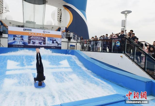 """11月13日,在皇家加勒比国际游轮的""""海洋量子号""""Flow Rider甲板上,极限运动达人张亮在急速奔腾的12米长海浪模拟器上乘风破浪,成功完成了15.874秒的头手倒立冲浪吉尼斯世界纪录的挑战,赢得现场阵阵欢呼。 中新社发 申海 摄"""