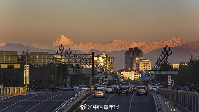 """诗圣杜甫笔下""""窗含西岭千秋雪""""的景色,近日在成都上演。在成都市温江区,有摄影师拍下了从城市眺望雪山的画面,还原了杜甫诗句描绘的壮美风光。(田相和 郑朝根 摄)"""