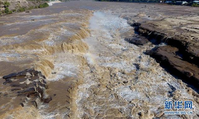 """这是10月11日无人机拍摄的壶口瀑布。 近日,位于晋陕大峡谷的黄河壶口瀑布水量持续增大,主副瀑布连成数百米的大瀑布,形成""""水岸齐平""""景观。 新华社发(饶北成 摄)"""