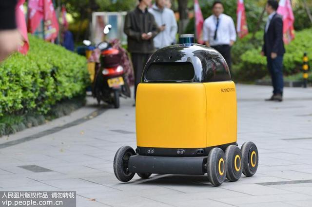 """2018年4月16日,苏宁物流在南京河西的滨江一号小区正式投放无人快递车,这是全国首个送货到家的无人车,也是国内首个可以实现室内室外场景无缝切换的无人车,不用人为控制,自己就能找到目的地,不仅能避让行人、车辆,还能自己乘电梯、叫门。这款萌萌的小黄车叫""""卧龙一号"""",采用六轮设计,车高在一米左右,承重30千克,最高时速可达60公里,爬坡高度35度,续航可达8小时,定位精度1-3厘米,可24小时为封闭园区提供无人配送服务。方东旭/摄"""