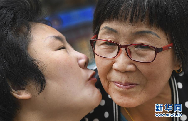 """5月10日,李艳华推着张娟(左)在小区散步,张娟对着婆婆喃呢道""""妈妈,我爱你。""""  2012年3月1日,陕西省铜川市的张娟在上班途中遭遇车祸,医生断定即使手术成功也是植物人。张娟经过4次手术才保住了性命,但一直昏迷不醒。  自此,张娟的婆婆李艳华挑起了照顾儿媳的重担。在李艳华的精心呵护下,张娟逐渐有了意识,慢慢有了简单的肢体反应。  2016年11月的一天,李艳华喂完张娟早餐后,张娟突然开口清楚地叫起""""妈妈"""",李艳华激动地泪流满面。  6年过去了,现在的张娟就跟牙牙学语的孩子一样,但只要有一点点进步,李艳华都特别开心。""""照顾了这么久,我们早从婆媳关系变成了亲亲的母女了。有我在一天,我就会照顾她一天"""",李艳华说。新华社记者陶明摄"""