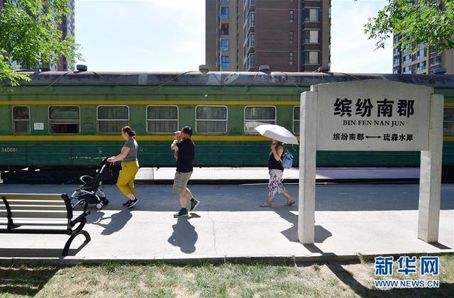 """6月13日,小区居民路过""""火车超市""""。在陕西省西安市高新区一小区内,一节摆放在一段铁轨上的绿皮火车车厢格外引人注目。这节车厢2013年在小区""""扎根"""",后来经营者接手将内部改为""""火车超市"""",外部的车次、车速、定员等信息全部原汁原味地保留。车厢旁还竖起了一块老式火车站牌,为居民带来独特的购物休闲体验。新华社记者邵瑞摄"""