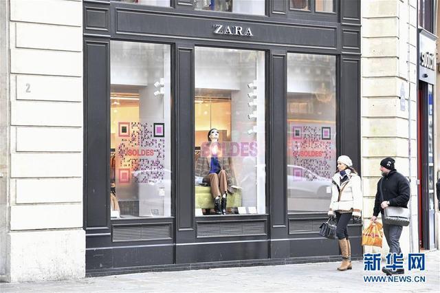 1月10日,行人在法国巴黎街头走过标有打折字样的橱窗。 法国大部分地区9日迎来冬季打折季。但由于品牌自主促销活动日益增加,法国民众对传统打折季反应日渐冷淡。 新华社发(杰克·陈 摄)