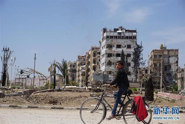 """4月16日,在叙利亚大马士革东郊杜马镇,一名儿童骑车经过杜马镇中心广场。叙利亚副外长费萨尔·梅克达德16日表示,叙政府愿意配合禁止化学武器组织(禁化武组织)就""""化武袭击""""展开调查,并为调查团的工作提供一切必要便利。4月7日,叙利亚首都大马士革东郊东古塔地区据称发生""""化武袭击""""事件。叙利亚外交部10日说,叙方已正式邀请禁化武组织派调查团进入东古塔地区杜马展开调查。新华社发(徐德智 摄)"""