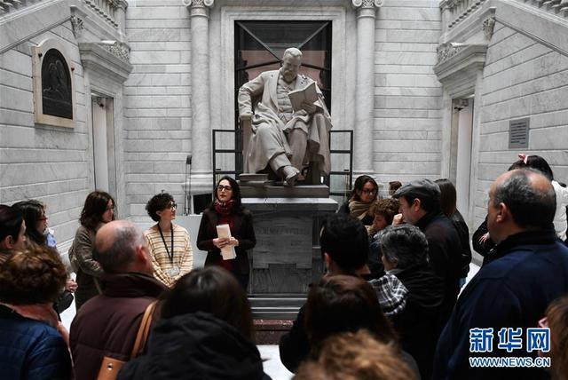 4月15日,市民在西班牙马德里的西班牙国家图书馆听讲解员介绍。  位于马德里的西班牙国家图书馆15日迎来一年一度的公众开放日。市民在工作人员的带领下,参观图书馆的阅览、藏书、办公、多媒体、古籍修复及历史陈列等区域。  新华社记者郭求达摄
