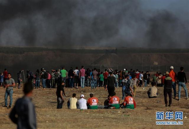 """5月15日,在加沙城以东的加沙地带与以色列交界地区,巴勒斯坦民众参加示威活动。  当日,在巴勒斯坦第70个""""灾难日""""到来之际,巴勒斯坦民众在多地举行抗议活动并与以色列军警发生冲突,两名巴勒斯坦人被以军士兵打死,约160人受伤。新华社发"""