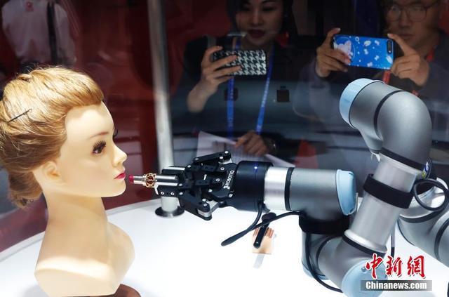 11月5日,在首届进博会的一展台上,一款美妆机器人吸引了许多女性参观者的目光。该机器人会画眉毛刷腮红,5分钟能完成一个妆容。当日,首届中国国际进口博览会在上海开幕,来自130多个国家和地区的3000多家企业前来参展。汤彦俊 摄