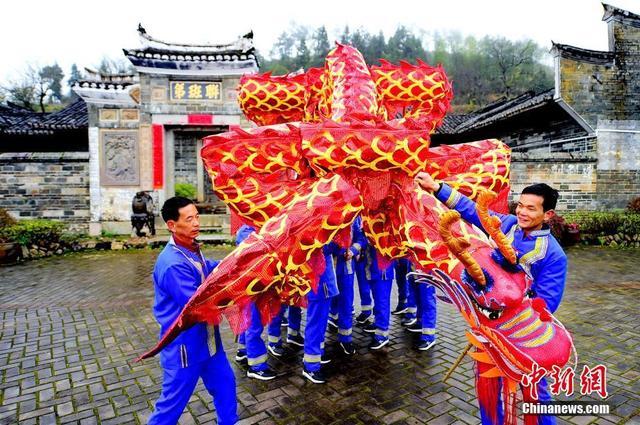 """2月10日,江西省会昌县洞头乡的畲族农民朋友在联班第前排练元宵舞龙会的""""摆字龙灯""""节目。会昌县的""""摆字龙灯""""是江西省非物质文化遗产项目,也是洞头畲族蓝氏的传统文化之一,距今已有300多年的历史。据了解,畲族""""摆字龙灯""""由7节或13节龙身(又称龙节)组成,每节龙身长1.0米,直径约0.5米,在每节龙身的中间固定一个把手,龙身外罩绘有龙鳞和龙爪的龙衣,颜色以红、黄为主。""""摆字龙灯""""舞动时,如同金龙翩翩起舞,龙身不断变换队形摆出汉字,组成吉祥祝福的词句,如""""天下太平""""""""安居乐业""""等。每逢重要节日、喜获丰收或有外族来客时,畲族群众都会舞动""""摆字龙灯""""进行庆祝或对来客表示尊敬和欢迎,更多的寓意是表达畲族人民的良好祝福。  朱海鹏 摄"""