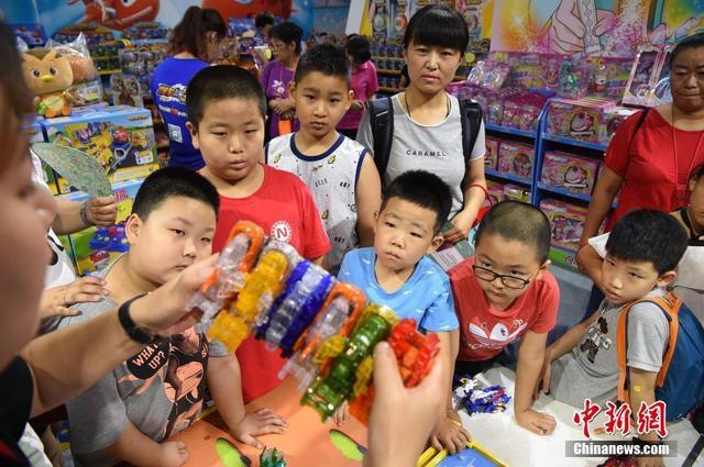 7月12日,2018中国玩博会·北京站(北京玩博会)在农业展览馆开幕,一些少年儿童被展区内的玩具所吸引。在至7月15日的会期内,全球30多个国家和地区的210个品牌的万款新品玩具将亮相。中新社记者 侯宇 摄