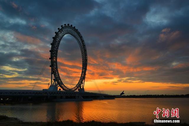 """位于山东潍坊滨海区白浪河入海口处的世界最大无轴式摩天轮""""渤海之眼""""5月16日正式投入使用。据工作人员介绍,""""渤海之眼""""摩天轮采用桥梁与摩天轮结合的形式,横跨白浪河,大桥全长540米,摩天轮矗立大桥中央,直径125米,总高度145米,有36个轿厢,每个轿厢能够坐8到10人,运行一周约需30分钟。游客除了乘坐摩天轮欣赏旖旎的海河风光,桥下空间还精心准备了五项顶级室内游乐项目。文/王勇钢 袁彦奎 图/袁彦奎"""