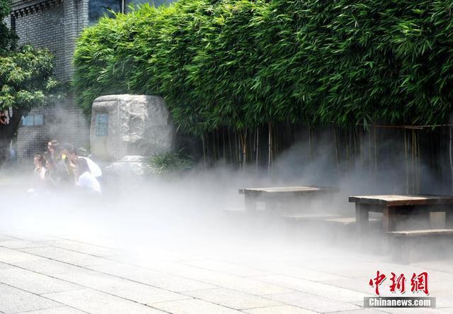 """5月15日,今年首轮高温天气正影响福建大部地区,为了给许多前来游玩的市民和游客消暑降温,福州三坊七巷景区启用了被称为""""大空调""""的喷水雾装置,为景区降温。当日,福建省气象台发布""""高温预警Ⅲ级""""。张斌 摄"""
