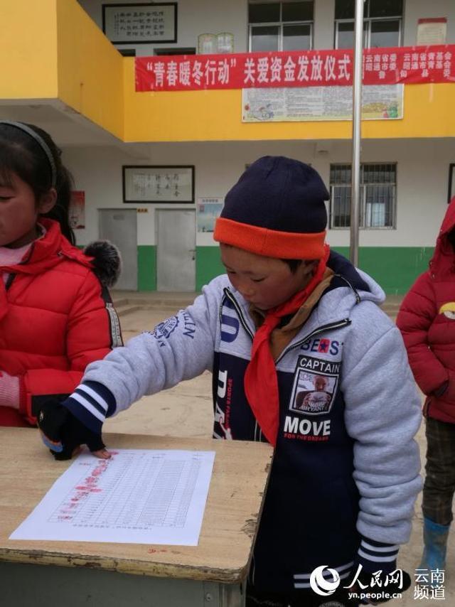 """云南""""冰花男孩""""所在学校收到首批10万元爱心捐款抵达鲁甸,图为穿上棉衣的""""冰花男孩""""小满。"""